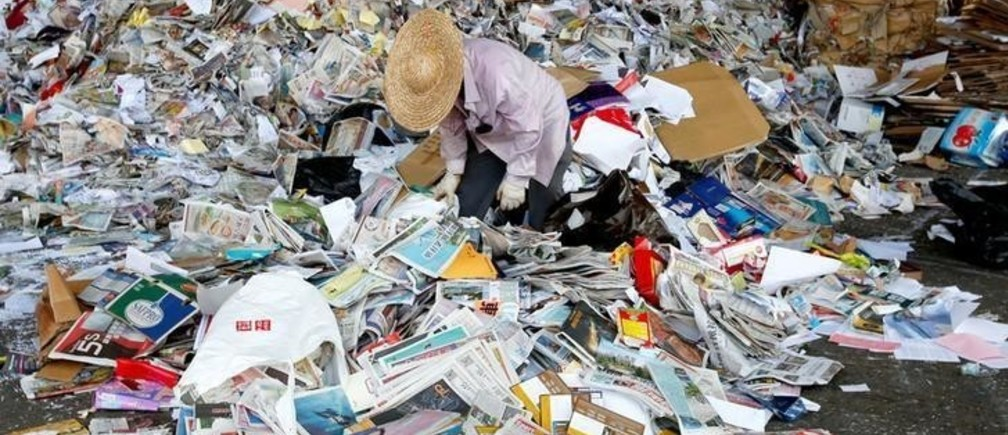 A worker picks rubbish from waste paper to be shipped to mainland China at a factory in Hong Kong, China September 19, 2017. Picture taken September 19, 2017.     REUTERS/Bobby Yip