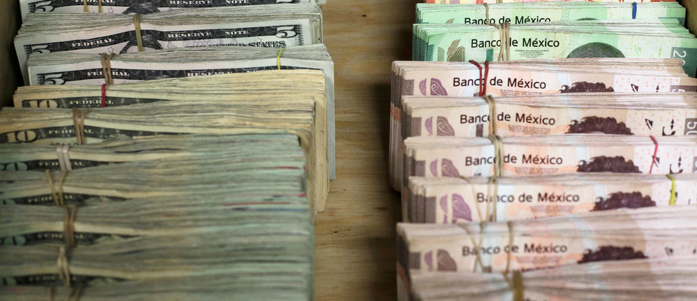 Bundles of banknotes of Mexican Peso and U.S. Dollar are pictured at a currency exchange shop in Ciudad Juarez, Mexico January 15, 2018. REUTERS/Jose Luis Gonzalez - RC1F0969F510