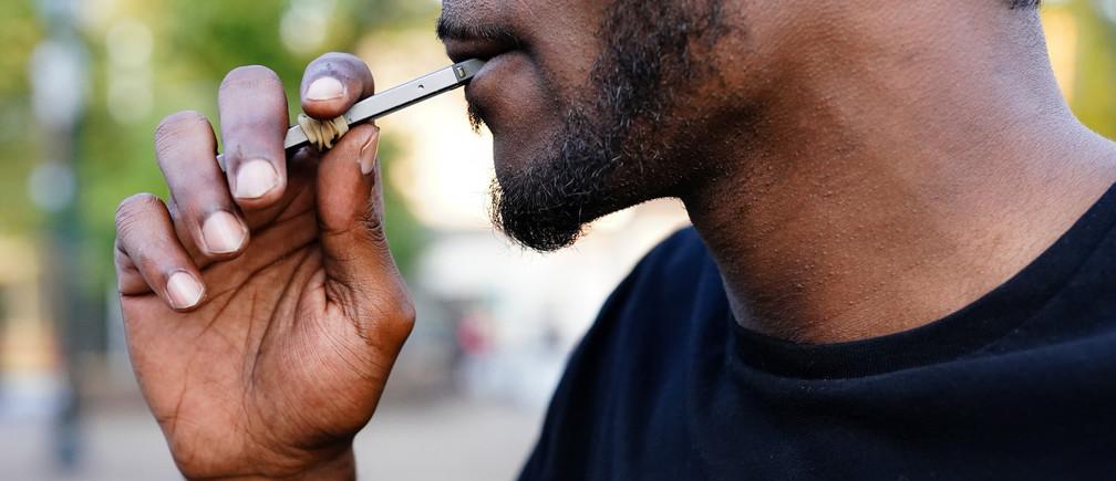 A man uses a Juul vaporizer in Atlanta, Georgia, U.S., September 26, 2019. Picture taken September 26, 2019.  REUTERS/Elijah Nouvelage - RC152429C950
