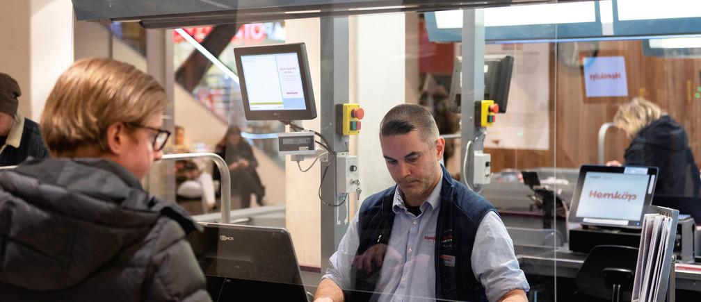 Un caissier travaille derrière un écran en plexiglas dans une épicerie, alors que la propagation de la maladie à coronavirus (COVID-19) se poursuit, à Stockholm, en Suède, le 31 mars 2020. Photo prise le 31 mars 2020.