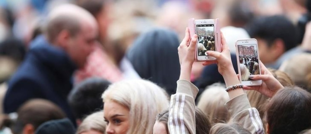 People use their mobile phones to photograph Britain's Prince William and Catherine, the Duchess of Cambridge greet well wishers as they leave The Karolinska Institute in Stockholm, Sweden January 31, 2018. REUTERS/Hannah McKay