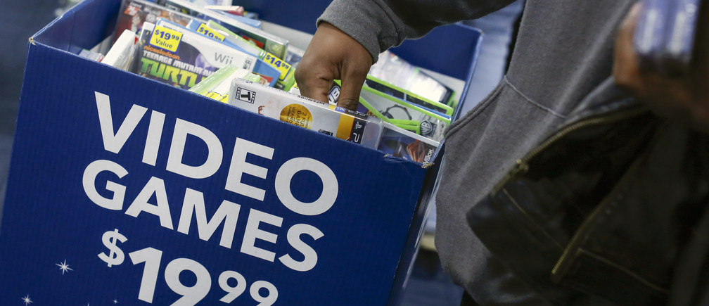 A shopper reaches in a discounted video game bin at a Best Buy store in Westbury, New York November 28, 2014. The Best Buy re-opened at 8am after opening Thanksgiving evening at 5pm and closing at 10 pm ahead of many other Black Friday retailers.REUTERS/Shannon Stapleton (UNITED STATES - Tags: BUSINESS) - GM1EABT00S401