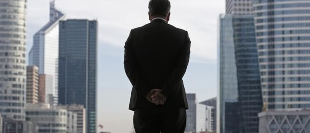 A Businessman is silhouetted as he stands under the Arche de la Defense, in the financial district west of Paris, November 20, 2012. France said its economy was sound and reforms were on track after credit ratings agency Moody's stripped it of the prized triple-A badge due to an uncertain fiscal and economic outlook. Monday's downgrade, which follows a cut by Standard & Poor's in January, was expected but is a blow to Socialist President Francois Hollande as he tries to fix France's finances and revive the euro zone's second largest economy.    REUTERS/Christian Hartmann (FRANCE - Tags: POLITICS BUSINESS)