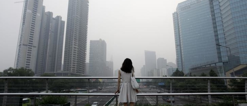 "A woman stands on an overhead bridge near the construction site of  ""Kaisa Plaza"", then named ""Changan No. 8"" (L), on a hazy day in Beijing's central business district in this July 28, 2012 file picture. Struggling Chinese developer Kaisa Group plunged further into crisis on Monday as several of its bank accounts were frozen and a number of creditors sought immediate repayment of debts. REUTERS/Jason Lee/Files (CHINA - Tags: ENVIRONMENT BUSINESS)"