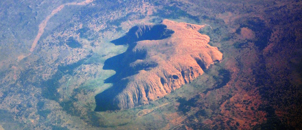 The Indigenous Australian community of Mutitjulu can be seen on the eastern side of Uluru, also known as Ayers Rock, in this aerial photo taken in the Northern Territory, Australia, June 14, 2016.     REUTERS/David Gray  - S1AETJZKNPAA