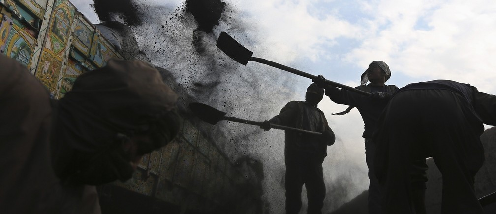 Labourers shovel coal onto a truck at a coal dump site outside Kabul January 23, 2014.