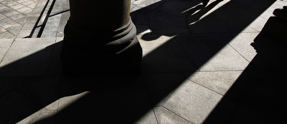 The shadow of a woman is cast at the Old Building of Bank of Japan's head office in Tokyo October 29, 2014. With just five months left before Governor Haruhiko Kuroda's self-imposed deadline for banishing deflation, the Bank of Japan is preparing for failure, and the first casualty could be its facade of board unity. Picture taken October 29, 2014. To match Insight JAPAN-ECONOMY/ REUTERS/Toru Hanai (JAPAN - Tags: BUSINESS TPX IMAGES OF THE DAY) - RTR4C3KX