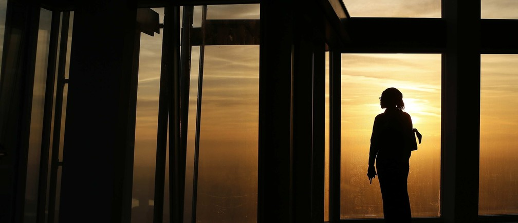An employee poses during sunrise as she looks out the window from The View gallery at the Shard, western Europe's tallest building, in London January 8, 2013. The View, the public viewing deck accessible by high speed elevators on the 309 metre (1,013 feet) Shard building, opens on February 1. Picture taken January 8, 2013.  REUTERS/Stefan Wermuth (BRITAIN - Tags: TRAVEL CITYSCAPE) - LM1E91A0RK201