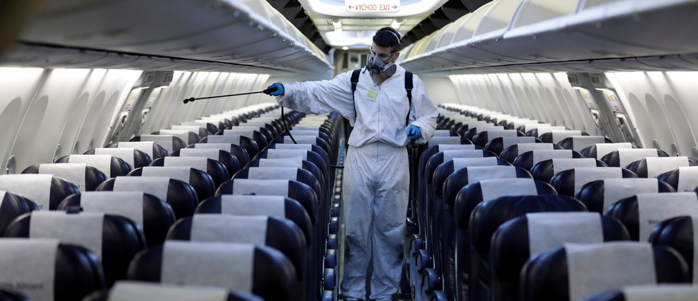 A worker in a protective suit disinfects a passenger plane of Smartwings airline at Vaclav Havel Airport due to the coronavirus disease (COVID-19) concerns in Prague, Czech Republic, May 21, 2020. REUTERS/David W Cerny - RC25TG9U8ZK3