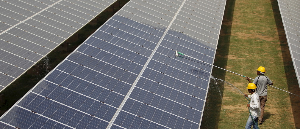 "Workers clean photovoltaic panels inside a solar power plant in Gujarat, India, in this July 2, 2015 file photo. The likely collapse of SunEdison Inc's solar project in India, the first of 32 planned ""ultra mega"" complexes, could delay Prime Minister Narendra Modi's goal to increase renewable energy fivefold by several years and probably cost consumers more. REUTERS/Amit Dave/Files - GF10000372053"