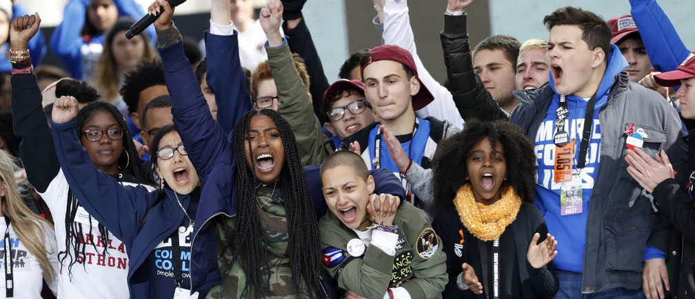 "Students and shooting survivors Tyra Hemans and Emma Gonzalez (3rd from R), from Marjory Stoneman Douglas High School in Parkland, Florida, and 11-year-old Naomi Wadler of Alexandria, Virginia (2nd from R), sing along with other students and shooting survivors at the conclusion of the ""March for Our Lives"" event demanding gun control after recent school shootings at a rally in Washington, U.S., March 24, 2018. REUTERS/Aaron P. Bernstein - HP1EE3O1IN7LM"