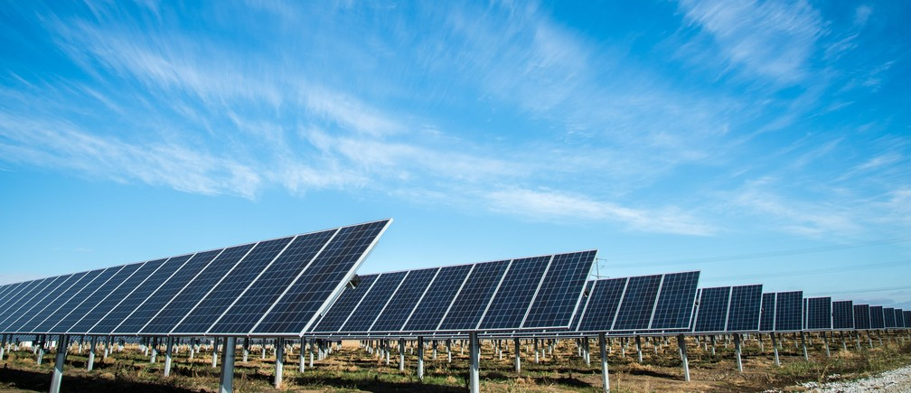 solar field showing solar panels against blue sky - american public power association