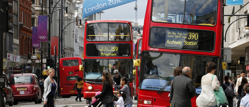 Double decker buses drive past posters of Olympic Rings and flags advertising the London 2012 Olympics at Oxford Street in London July 13, 2012. The London 2012 Olympics run from July 27 to August 12.  REUTERS/Fabrizio Bensch (BRITAIN - Tags: SPORT OLYMPICS TRANSPORT) - GM1E87D1QRW01