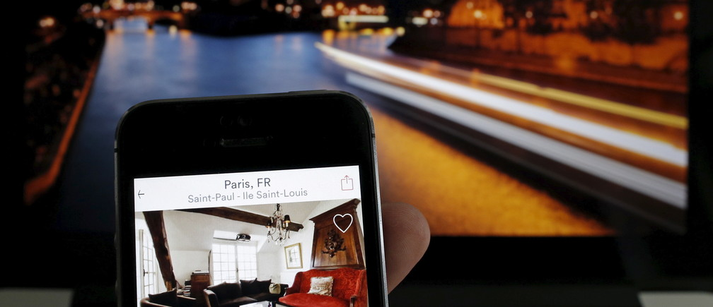 An illustration picture shows the Paris apartment offer by American actress Judith Freiha on the Airbnb web page displayed on a smatphone in front of a general view of the Ile Saint-Louis on the Seine river in Paris, France, August 9, 2015. Nowhere in the world has more accommodation available on Airbnb than Paris. Now the home-sharing website that has transformed budget travel to the French capital is giving its super-deluxe hotels a fright too.     REUTERS/Christian Hartmann  - RTX1NNYQ