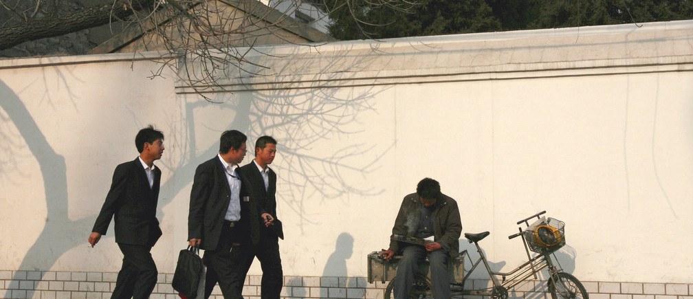 Three businessmen walk past a labourer resting on a bicycle along a street in Beijing December 17, 2007. China, obsessed with maintaining stability, is grappling with an acknowledged rise in social unrest, sparked by anger at a growing rich-poor divide, official corruption, pollution and land grabs without proper compensation. The government is determined to keep such problems under control ahead of the 2008 Beijing Olympics.   REUTERS/David Gray      (CHINA) - GM1DWVHZEXAA