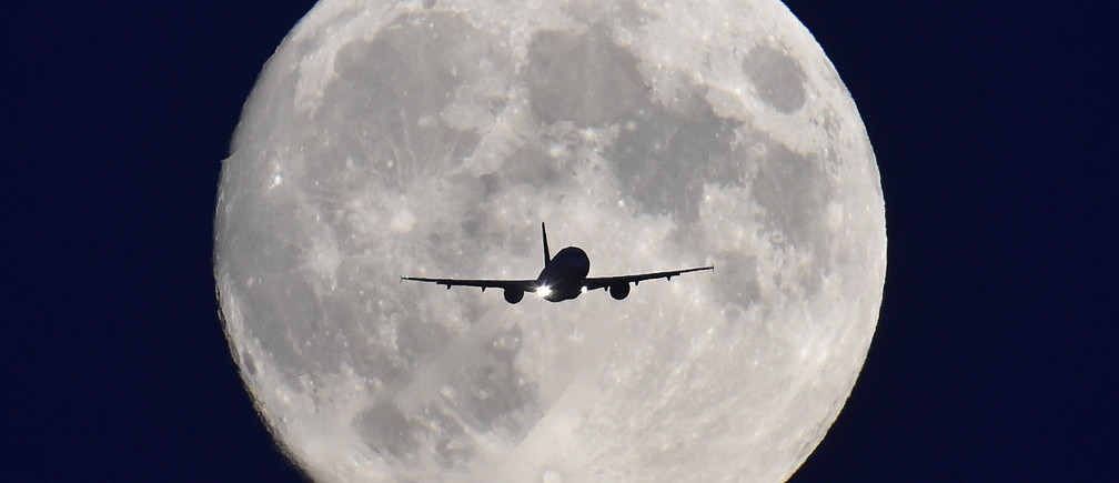 A passenger plane passes in front of the full moon as it makes a final landing approach to Heathrow Airport in west London, October 7, 2014.  Heathrow Airport Holdings (HAH) is set to sell three British airports for 1 billion pounds ($1.6 billion) to a group including Spanish infrastructure firm Ferrovial, Singapore sovereign fund GIC and Australian bank Macquarie, according to Sky News. The sale of the three regional airports would leave HAH with just Heathrow, the west London hub that ranks as Britain's busiest and the world's third busiest airport. HAH would then be free to focus on its plan to gain government approval to build a third runway at Heathrow, an issue which has been at the centre of a long-running political tussle. REUTERS/Toby Melville (BRITAIN - Tags: BUSINESS TRANSPORT) - GM1EAA80BCJ01
