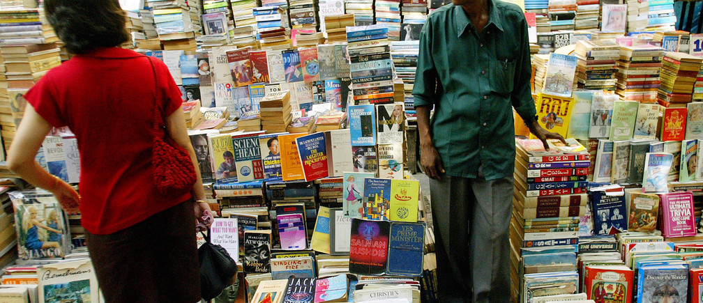 An Indian bookseller looks on in his bookshop as a customer browses through books on a pavement in Bombay on May 24, 2005. India's financial capital, renowned for its vibrant street activity and nightlife, has cleared out dozens of hawkers selling used and pirated copies of novels and magazines along a bustling thoroughfare. To match feature Life-India. REUTERS/Punit Paranjpe   PP/NL - RP6DRNATNPAA