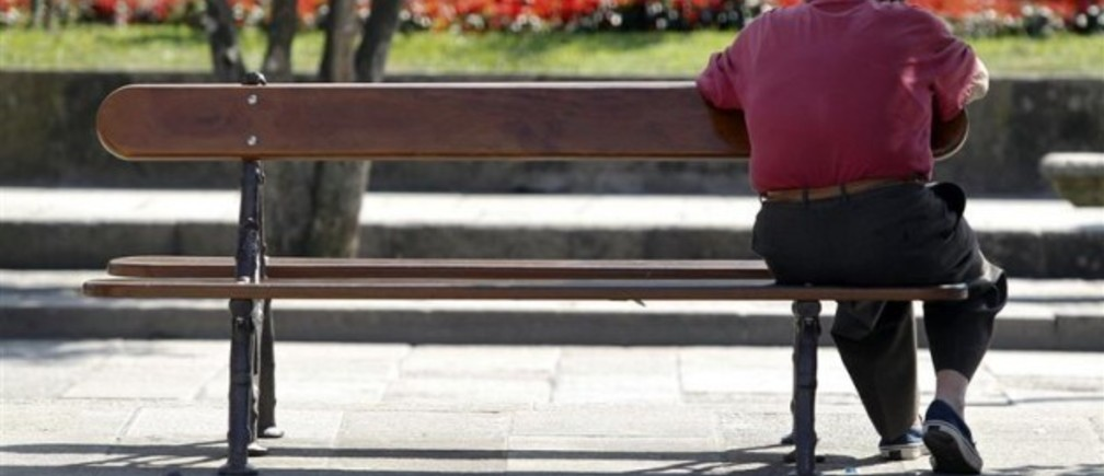 A man sits on a bench in central Pontevedra September 18, 2012. Spain is considering freezing pensions and speeding up a planned rise in the retirement age as it races to cut spending and meet conditions of an expected international sovereign aid package, sources with knowledge of the matter said. Picture taken September 18.