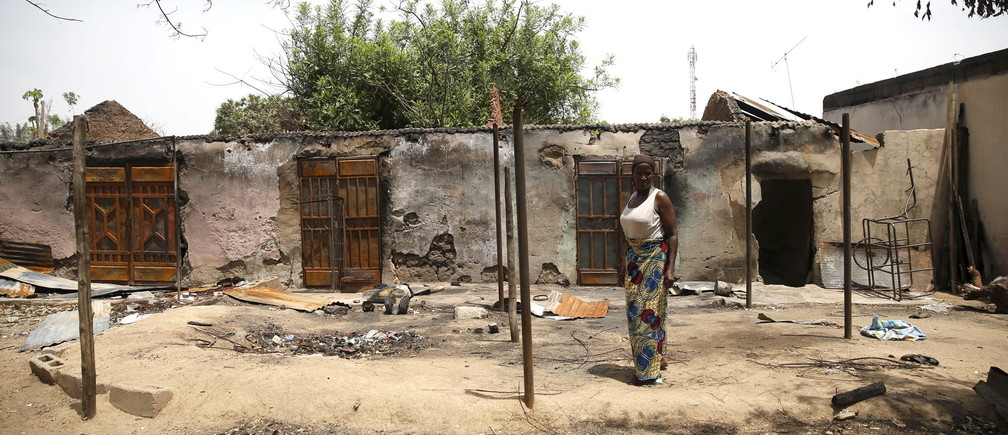 A woman stands in front of a burnt building in Michika town, after the Nigerian military recaptured it from Boko Haram, in Adamawa state May 10, 2015.