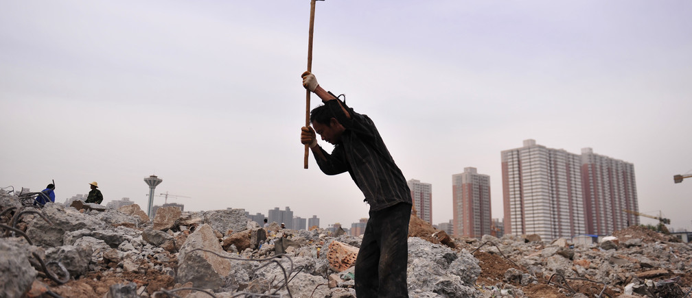 A labourer swings a sledgehammer to smash concrete to recycle steel bars at a demolition site near a residential complex in Xi'an, Shanxi province June 8, 2012. China's main real estate regulator reaffirmed its commitment to maintaining current restrictions on property sales on Wednesday, the official Xinhua news service reported, as Beijing continues to resist calls for wider easing to offset a slowing economy. REUTERS/Rooney Chen (CHINA - Tags: BUSINESS REAL ESTATE) - GM2E8681J2B01