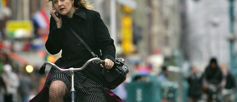 A women talks on her mobile phone while riding a bike in Amsterdam January 17, 2007. REUTERS/Koen van Weel (NETHERLANDS)