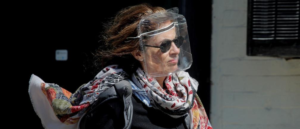 Una mujer lleva un recipiente de plástico para alimentos para protegerse durante el brote de la enfermedad coronavirus (COVID19) en el distrito de Brooklyn de Nueva York, EE.UU., el 11 de abril de 2020.
