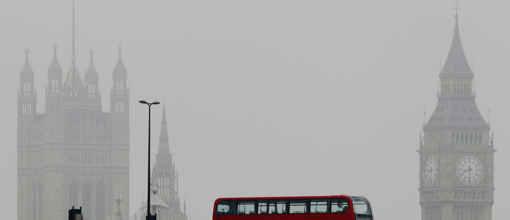 A bus crosses Waterloo bridge in front of the Houses of Parliament during a misty morning in London April 13, 2012.   REUTERS/Luke MacGregor  (BRITAIN - Tags: CITYSPACE POLITICS TRANSPORT ENVIRONMENT) - RTR30O79