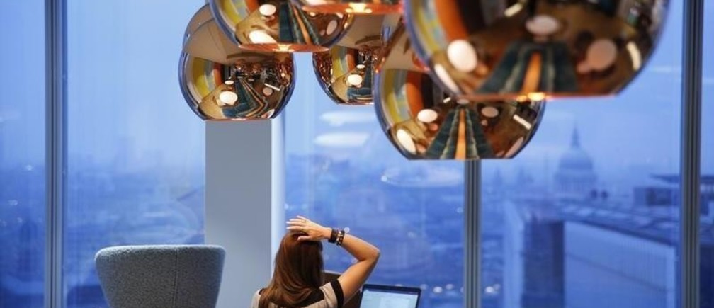 A worker takes in a view of St Paul's cathedral as she works in the bar of the Jellyfish office space in London, Britain December 19, 2016. Picture taken December 19, 2016. REUTERS/Neil Hall