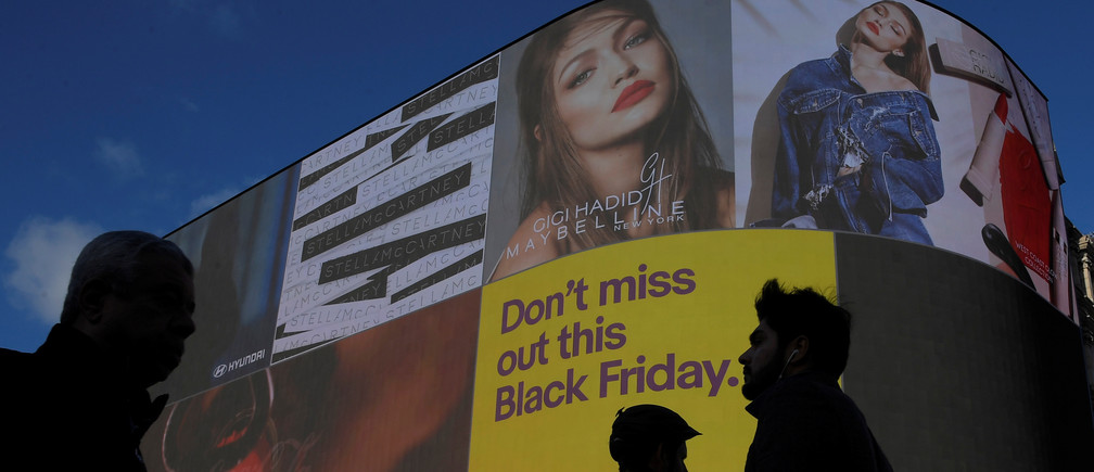 Shoppers are seen walking past the electronic billboard at Piccadilly Circus, showing retail adverts incuding one for 'Black Friday' in London, Britain, November 23, 2017. REUTERS/Toby Melville - RC14BDFDA300