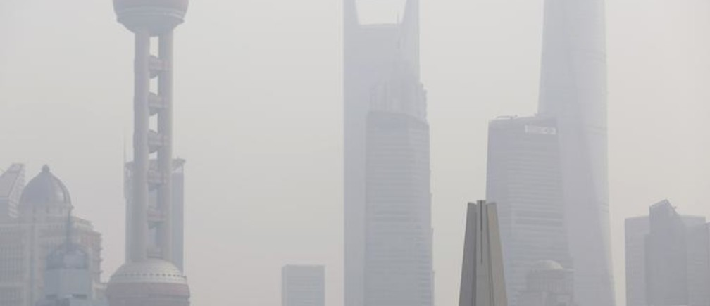 A man wearing a face mask stands on a bridge in front of the financial district of Pudong on a hazy day, in Shanghai November 17, 2014. REUTERS/Aly Song (CHINA - Tags: ENVIRONMENT SOCIETY CITYSCAPE BUSINESS TPX IMAGES OF THE DAY)