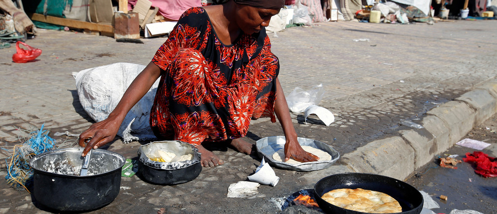 A woman displaced by the war in Yemen cooks on a street in Hodeida
