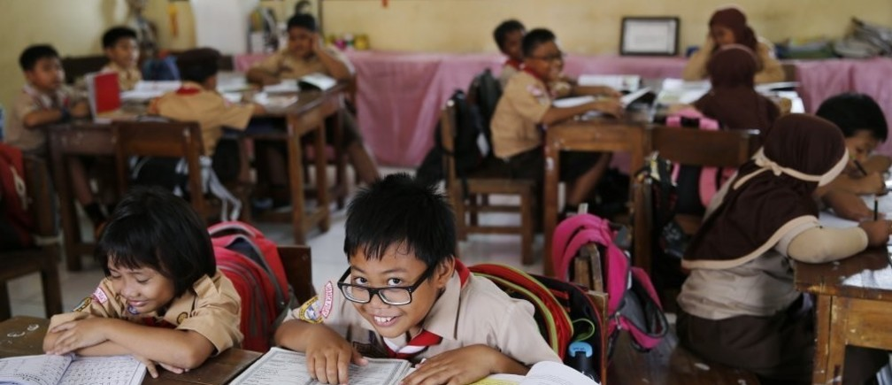 A student reacts to the camera as a teacher teaches in Jakarta, Indonesia.