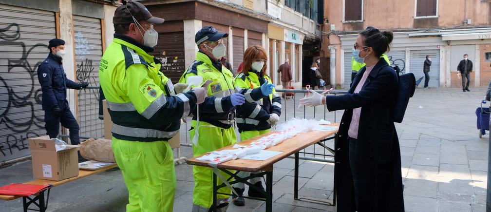 Trabajadores municipales distribuyen máscaras y guantes en el mercado de Rialto, ya que la región del Véneto impuso nuevas restricciones a los mercados al aire libre para evitar la propagación de la enfermedad coronavirus (COVID-19), en Venecia, Italia, el 4 de abril de 2020.