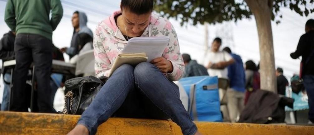 An unemployed woman fills a job application at a parking lot  in Ciudad Juarez, Mexico, November 7, 2017. Picture taken November 7, 2017. REUTERS/Jose Luis Gonzalez