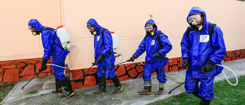 Health workers wearing protective suits spray disinfectant outside of a building during an awareness campaign for coronavirus disease (COVID-19), in Jalalabad, Afghanistan  March 19, 2020. REUTERS/Parwiz - RC2UMF9ZSPFY