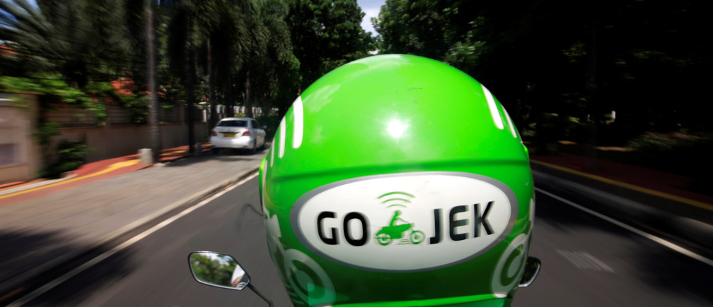 A Go-Jek driver rides a motorcycle on a street in Jakarta, Indonesia, December 15, 2017. REUTERS/Beawiharta - RC14B409FEA0