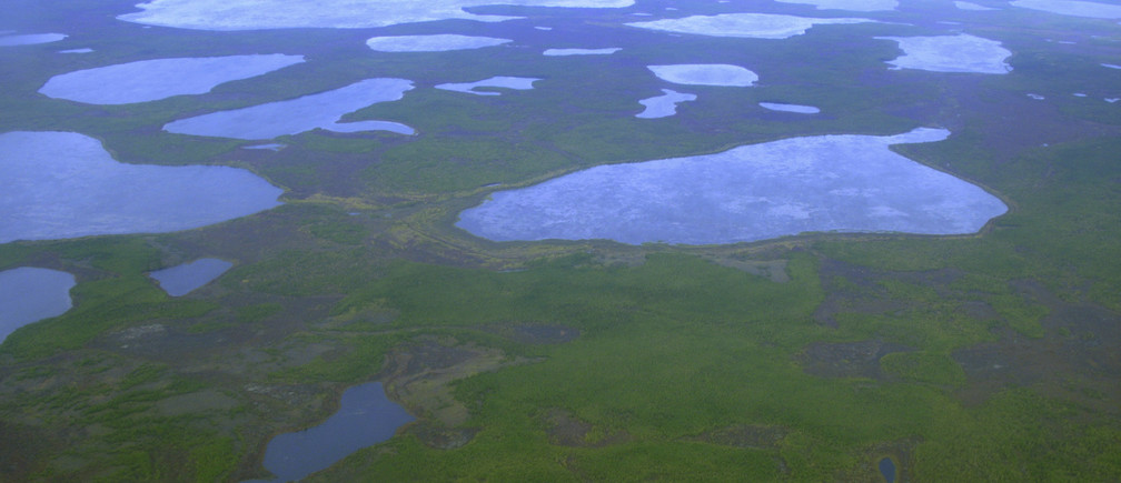 An aerial view shows thermokarst lakes outside the town of Chersky in northeast Siberia August 28, 2007. For millennia, layers of animal waste and other organic matter left behind by the creatures that used to roam the Arctic tundra have been sealed inside the frozen permafrost. Now climate change is thawing the permafrost and lifting this prehistoric ooze from suspended animation. Zimov, a scientist who for almost 30 years has studied climate change in Russia's Arctic, believes that as this organic matter becomes exposed to the air it will accelerate global warming faster than even some of the most pessimistic forecasts.  Picture taken August 28, 2007.  To match feature ARCTIC-RUSSIA/PERMAFROST   REUTERS/Dmitry Solovyov (RUSSIA) - GM1DWEBZDFAA
