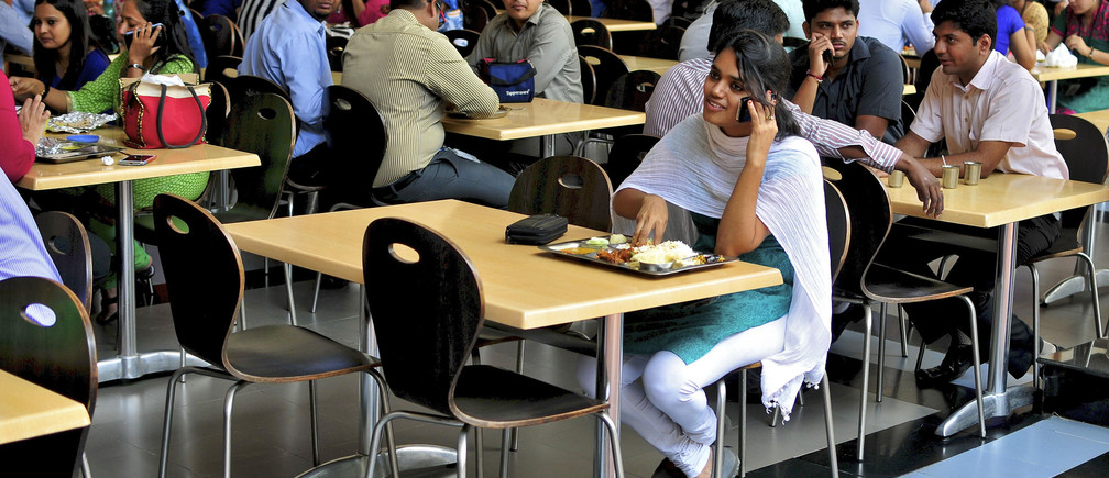An employee speaks on a mobile phone as she eats her lunch at the cafeteria in the Infosys campus in the southern Indian city of Bangalore September 23, 2014. Infosys Ltd's new CEO Vishal Sikka has come up with a novel approach to reviving the financial fortunes of India's trailblazing outsourcing firm: use Facebook at work, tweet, but get the job done. Infosys has long been run as a conservative company known for keeping strict tabs on work hours and sometimes fining employees for not wearing ties on specific days. Such cheerless self-regard could not have come at a more challenging time, analysts say. To retain talent, Sikka hopes to create a more employee-friendly workplace. To match story INFOSYS-CEO/STRATEGY   REUTERS/Abhishek Chinnappa (INDIA - Tags: BUSINESS EMPLOYMENT SCIENCE TECHNOLOGY) - GM1EA9O0EM501