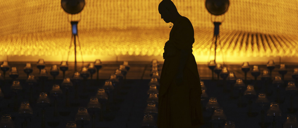 A Buddhist monk arrives before others for an alms offering ceremony on Makha Bucha Day at the Wat Phra Dhammakaya temple in Pathum Thani province, north of Bangkok March 4, 2015. The Dhammakaya temple members include some of Thailand's most powerful politicians and is regarded as the country's richest Buddhist temple. Makha Bucha Day honours Buddha and his teachings, and falls on the full moon day of the third lunar month.  REUTERS/Damir Sagolj (THAILAND - Tags: SOCIETY RELIGION) - GM1EB3414H501