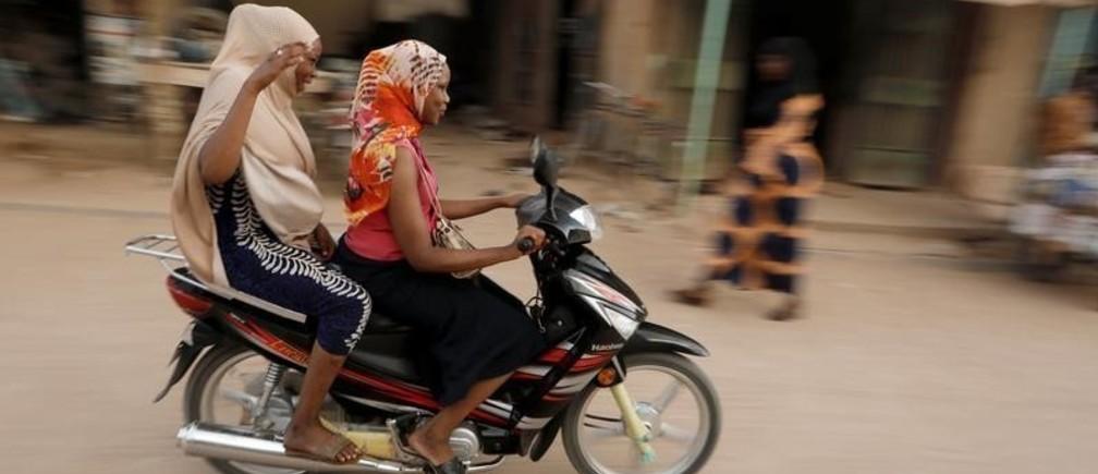 Women ride a motorcycle along the market in Agadez, Niger October 29, 2019.REUTERS/ Zohra Bensemra - RC1C690EFC30