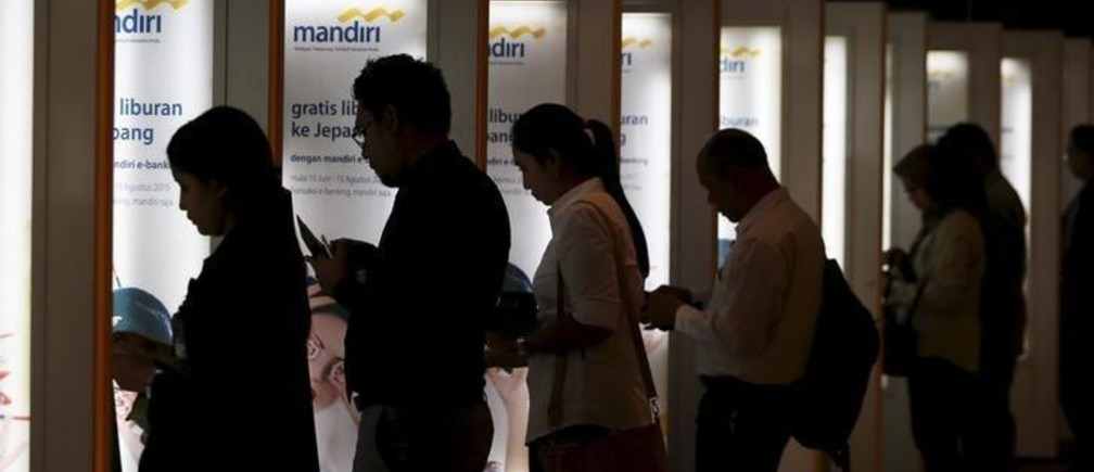 People use Bank Mandiri ATMs at the Mandiri Tower building in Jakarta August 25, 2015.   Indonesia's central bank governor said that Bank Indonesia was always in the market to stabilise the rupiah's movements against the dollar and will not take part in competitive devaluation. REUTERS/Beawiharta
