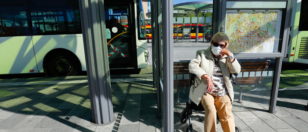 An elderly woman with a protective mask sits at a bus-stop, as the spread of the coronavirus disease (COVID-19) continues in Hanau, Germany, April 20, 2020. REUTERS/Ralph Orlowski - UP1EG4K0QX01M