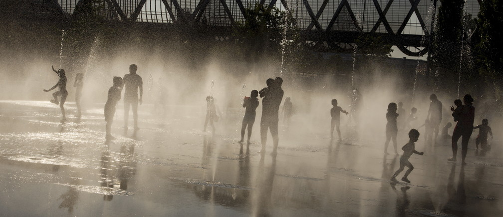 People play while cooling off in a public fountain as temperatures soar to around 40 degrees Celsius (104 degrees Fahrenheit) in central Madrid, Spain, July 13 2015. State meteorological office Aemet said on Wednesday it expected extreme temperatures above 40 degrees Celsius in central provinces for at least another week. REUTERS/Juan Medina      TPX IMAGES OF THE DAY      - RTX1K90U