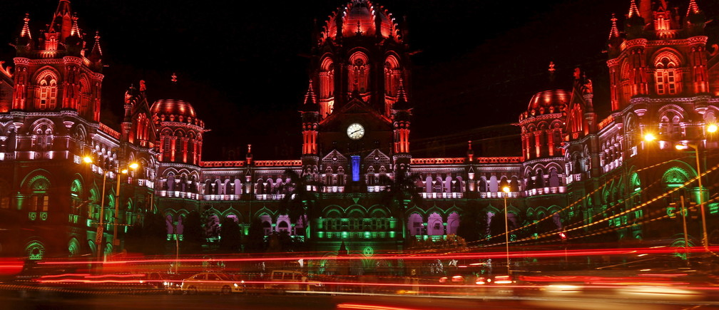 Traffic moves in front of the Chhatrapati Shivaji Terminus railway station as it is illuminated with the colours of the Indian flag in lieu of Independence Day in Mumbai, India, August 15, 2015.