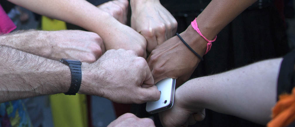 Activist Austin Guest and others join fists in solidarity ahead of a protest march in New York May 1, 2012.