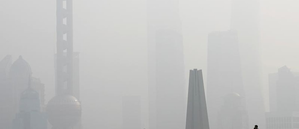 People walk on a bridge in front of the financial district of Pudong, which is covered in smog, during a polluted day in Shanghai, China November 28, 2018. REUTERS/Aly Song       TPX IMAGES OF THE DAY - RC1D4A8F7BB0