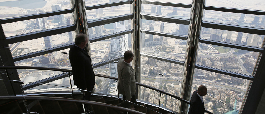 Businessmen walk down the stairs at the 123rd floor of the Burj Khalifa, the tallest building in the world, in Dubai.
