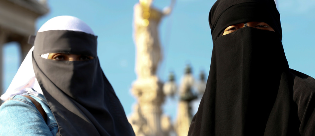 "Demonstrators covering their faces participate in a protest called ""The traditional clown's walk against the burqa ban"" in Vienna, Austria October 1, 2017.   REUTERS/Leonhard Foeger - RC1F47DF98D0"
