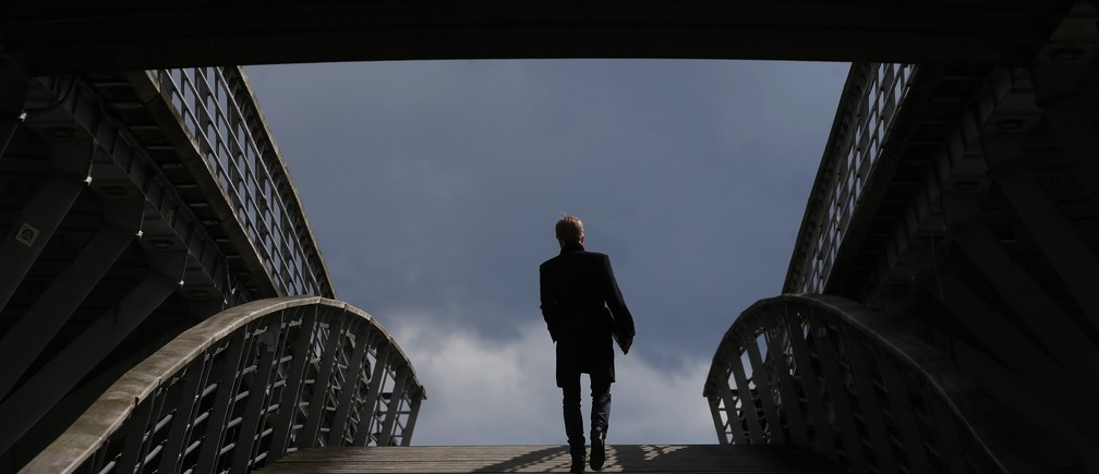 A businessman is seen in silhouette as he crosses the Solferino Bridge, over the Seine river, after the close of businesses in Paris, France, May 20, 2015.