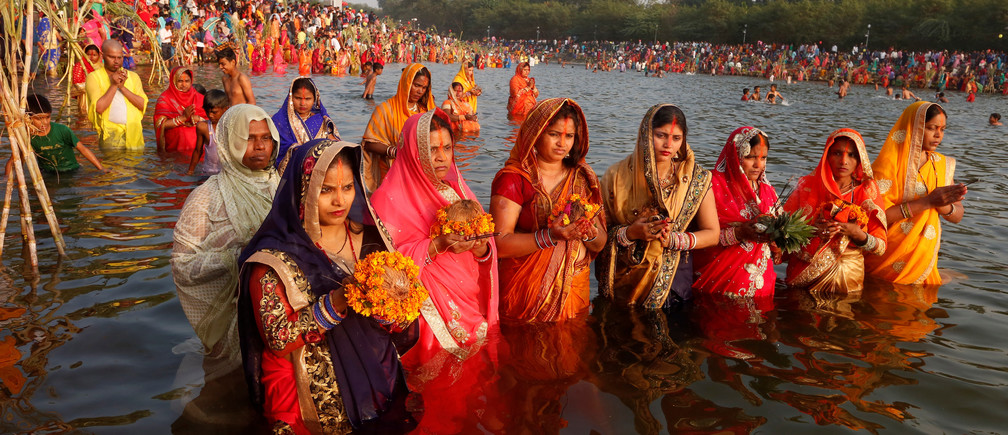 Hindu women hold offerings as they worship the Sun god in the waters of a lake during the Hindu religious festival of Chhath Puja in Chandigarh, India, India, November 13, 2018. REUTERS/Ajay Verma - RC16BF577B60